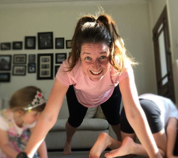 Woman doing exercises with her kids in the livingroom