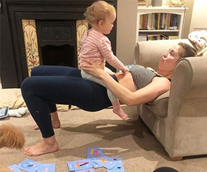 Woman exercising on her sofa with baby on her tummy
