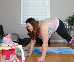 Woman doing yoga on a mat with her baby