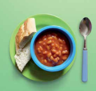 bowl of baked beans with a french stick roll on the side
