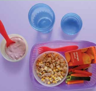 Image of a packed lunch with a bowl of tuna and sweetcorn pasta, a yoghurt pot, vegetable sticks and a carton of orange juice.