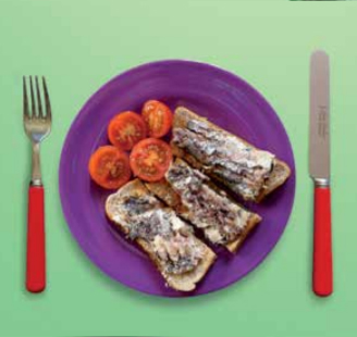 Image of a plate of sardines on toast with a tomato
