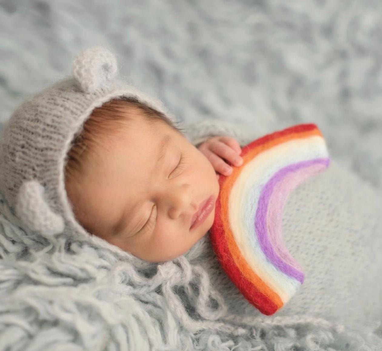 Anita's rainbow baby, Rumi, holding a rainbow