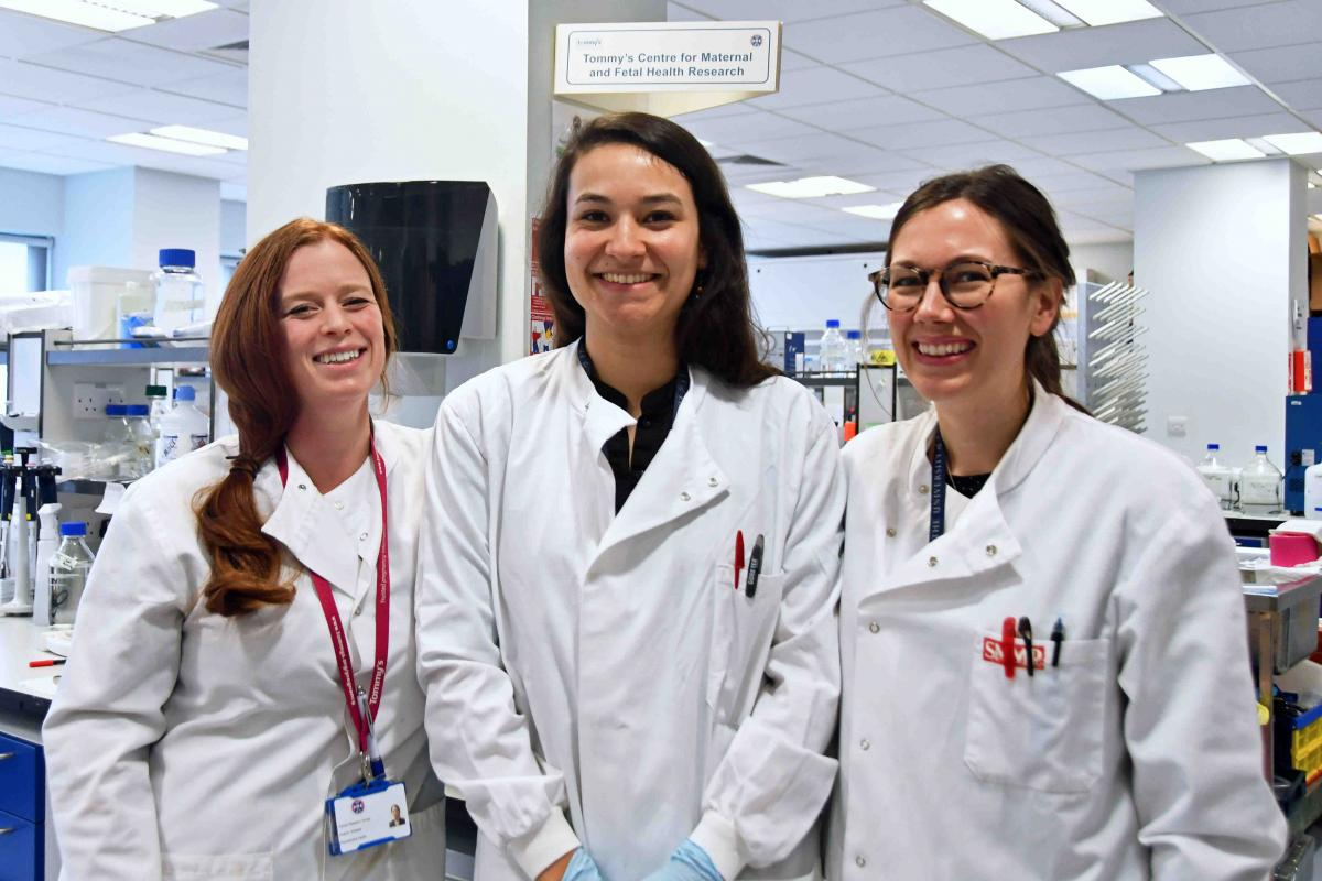 Three smiling female researchers wearing lab coats in a science lab